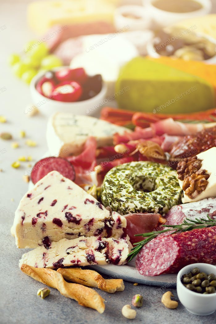 Cutting board with salami, cold smoked meat, prosciutto, ham, cheeses on grey background. Cheese and