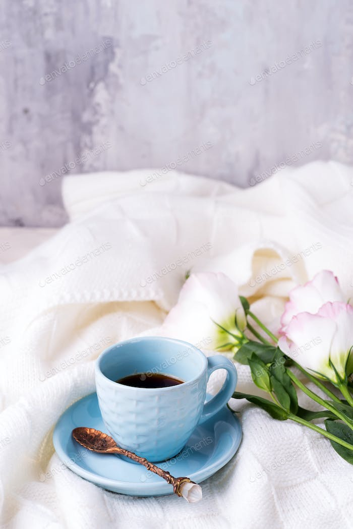Having a cup of coffee with chocolate, flowers eustoma on blanket in bed. Holiday concept