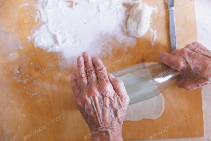 Hands of an old woman flattening dough