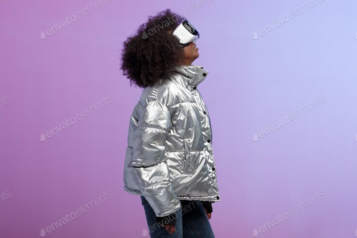 Mod curly brown-haired girl dressed in a silver-colored jacket uses the virtual reality glasses in
