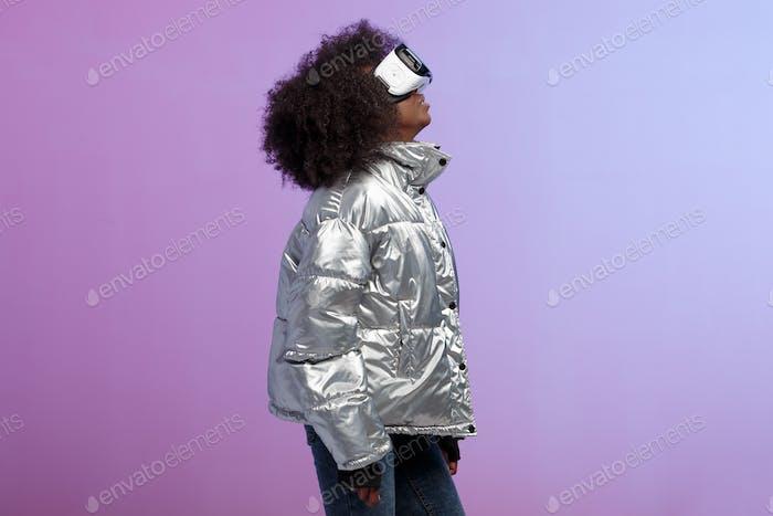 Mod lockiges braunhaariges Mädchen in einer silberfarbenen Jacke gekleidet verwendet die Virtual Reality Brille in