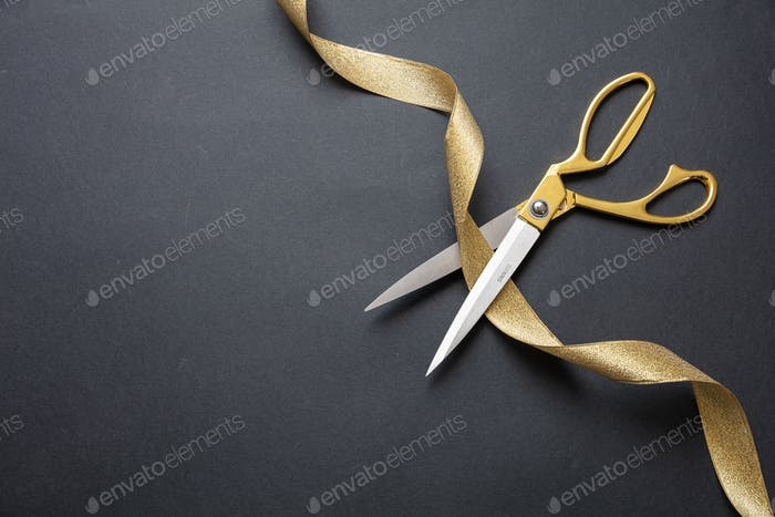 Grand opening. Gold scissors cutting gold satin ribbon, black background