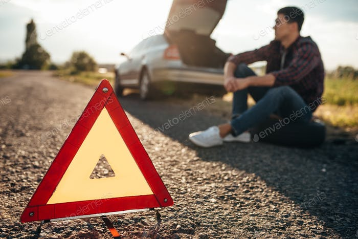 Broken car concept, breakdown triangle on road