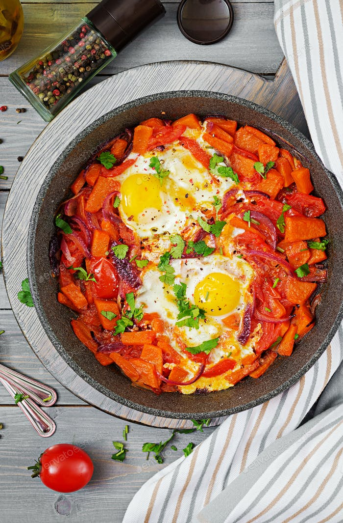 Fried eggs with pieces of pumpkin, red onions and tomatoes. Tasty breakfast. View from above