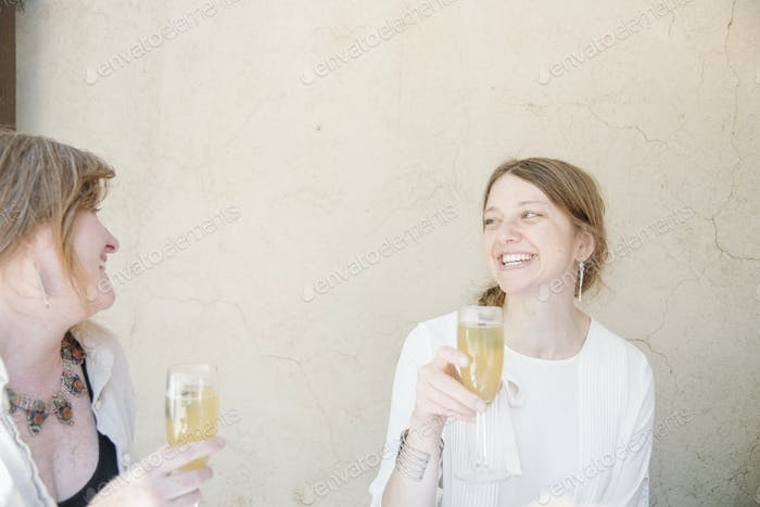 Two women sitting at a table, smiling at each other, holding glasses of champagne.