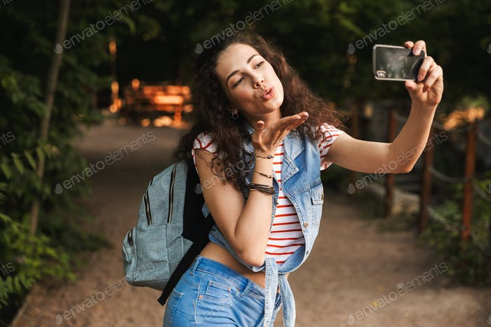 Photo of beautiful teenage woman 18-20 with backpack, blowing ai