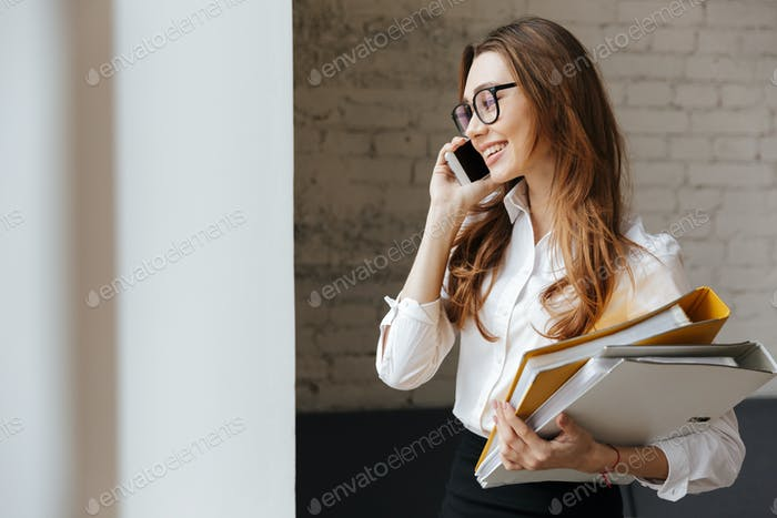 Cheerful business woman indoors talking by mobile phone
