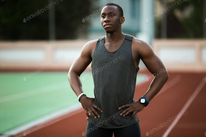 Young male athlete standing at the stadium race track