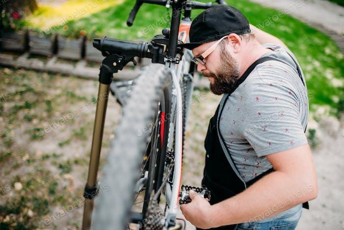 Repairman works with bike wheel, cycle workshop