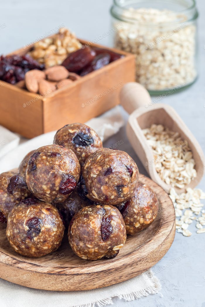 Healthy energy balls with cranberries, nuts, dates and rolled oats on wooden plate, vertical