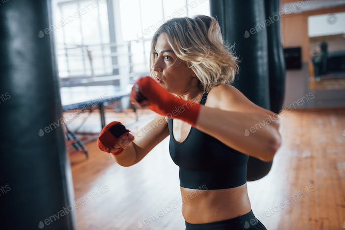 Self defence sports. Female boxer is punching the bag. Blonde have exercise in the gym