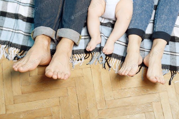 Füße der jungen Familie auf dem Boden