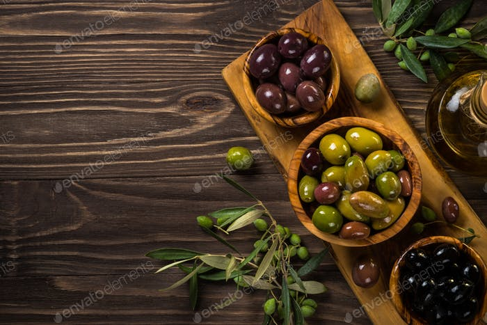 Black and green olives on wooden table