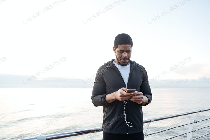 Sportsman listening to music from cell phone on pier