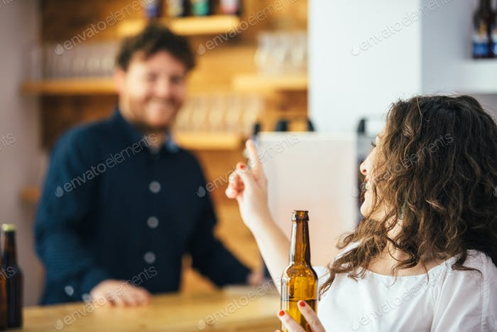 Woman with bottle talking to bartender