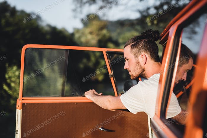 A young man getting out of a car on a roadtrip through countryside.
