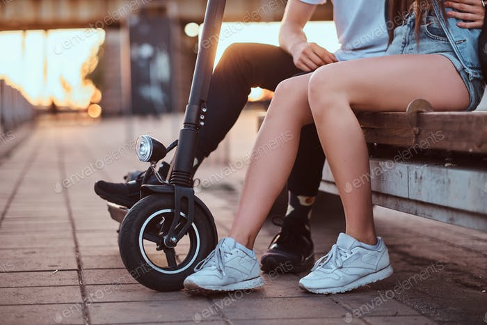 Couple of young people are chilling with their scooters