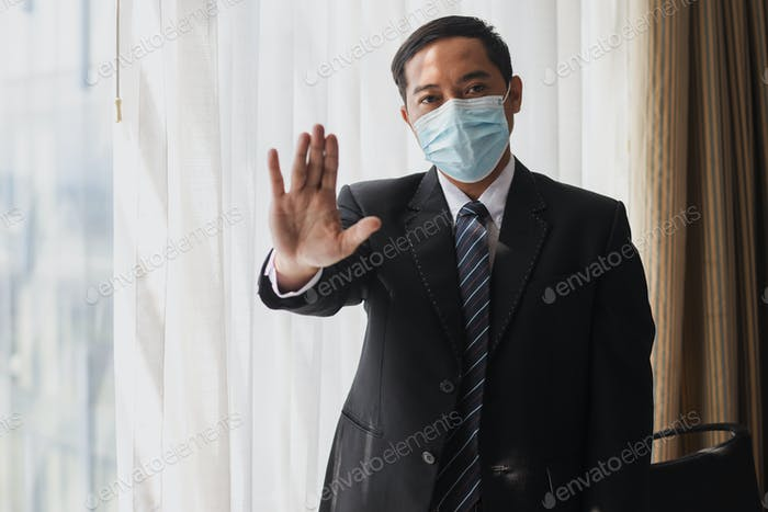 Stop hand by businessman wearing medical mask