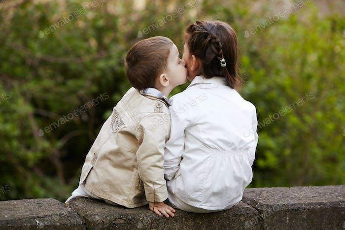 hübsches Kind fiel schön und glücklich es ist erster Kuss