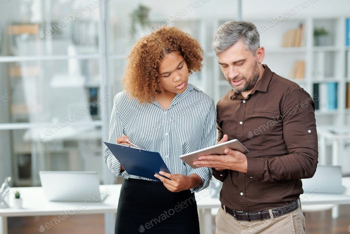 Two contemporary bankers checking financial data on paper and in tablet