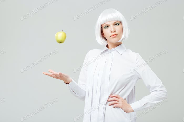 Beautiful woman standing and throwing apple in the air