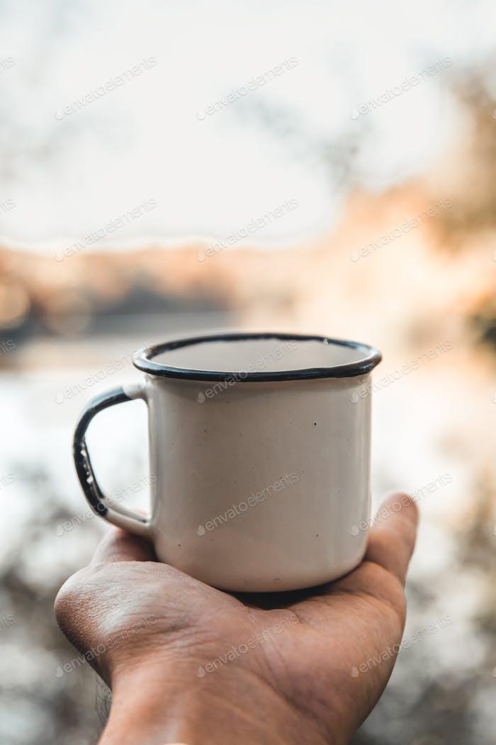 Hand hält Tasse Kaffee auf natürlichem Hintergrund