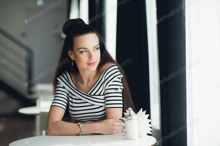 Portrait of an adult beautiful woman looking through window while sitting at a table in a cafe.
