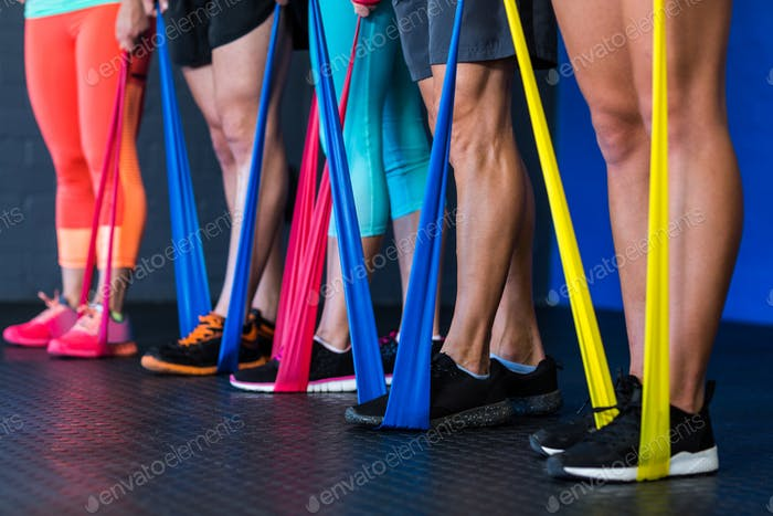 Athletes exercising with resistance band in gym