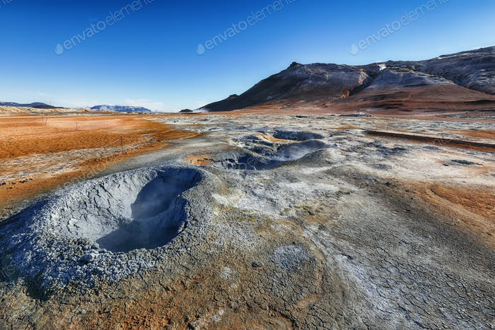 Boiling mudpots in the geothermal area Hverir and cracked ground around.