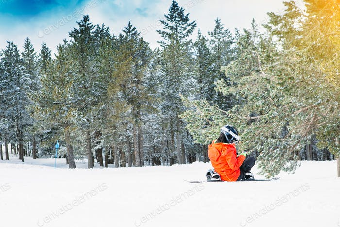 Snowboarder uses the mobile phone at the ski resort