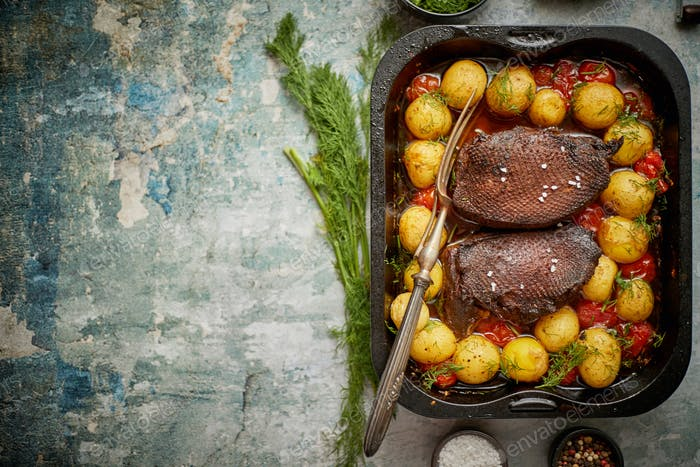 Roasted duck breast with golden crispy skin served with baked potatoes, sprinkled with dill