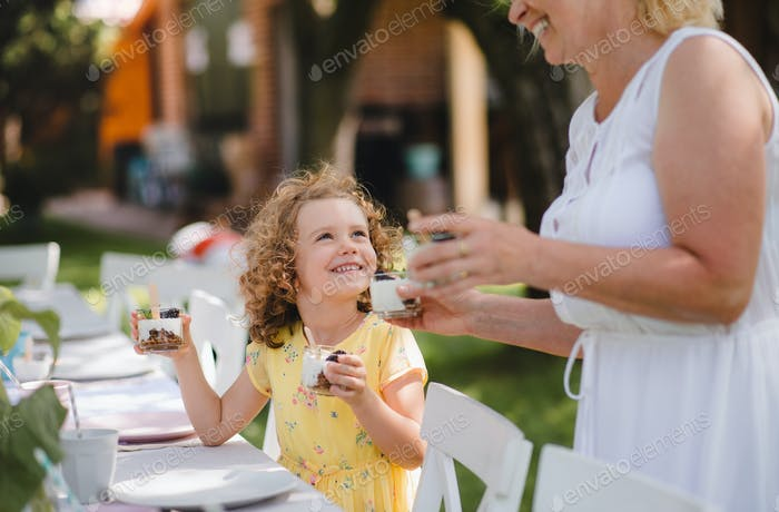 Small girl with grandmother outdoors on garden party in summer, eating.