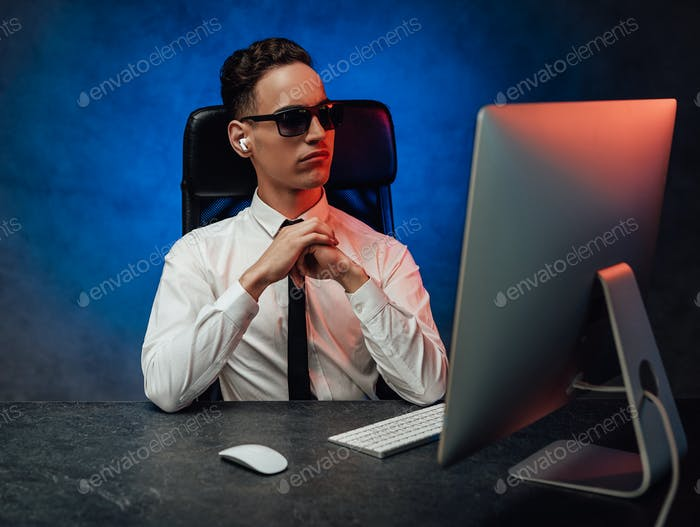 A young office worker in in formalwear and sunglasses sits in the workplace