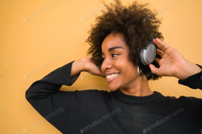 Young afro woman listening to music with headphones.