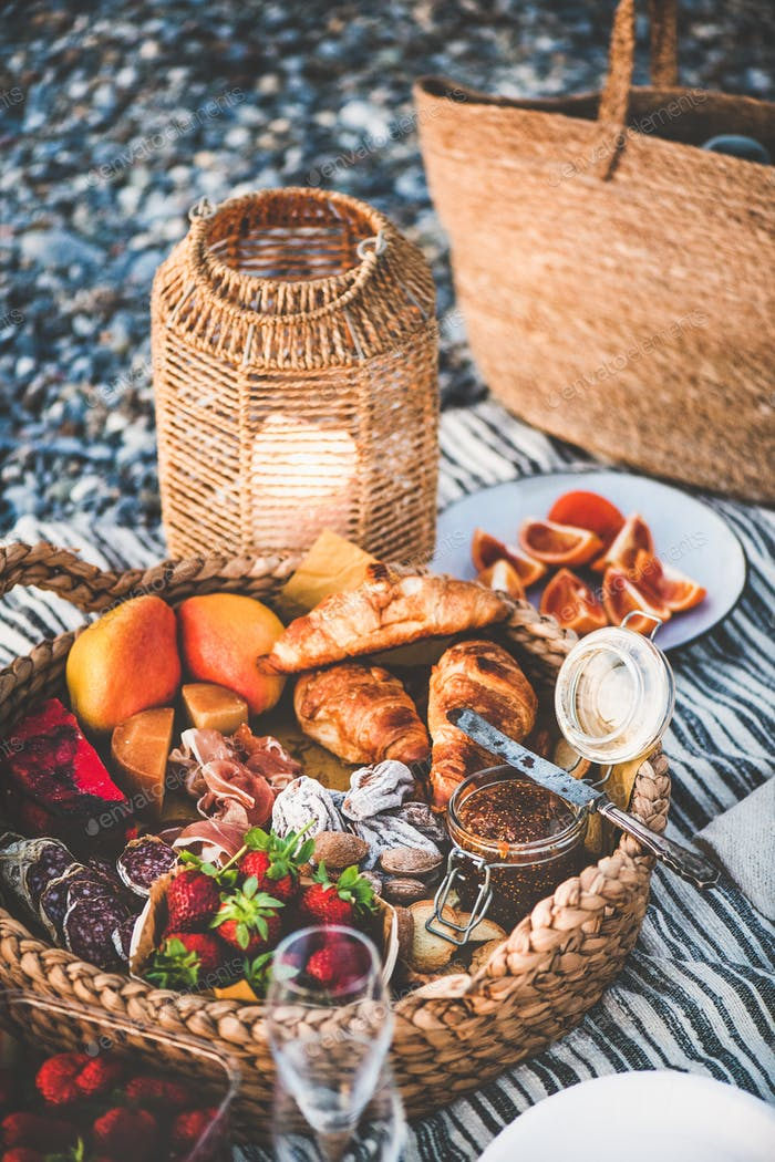 Summer picnic concept with tasty appetizers, fruits and croissants