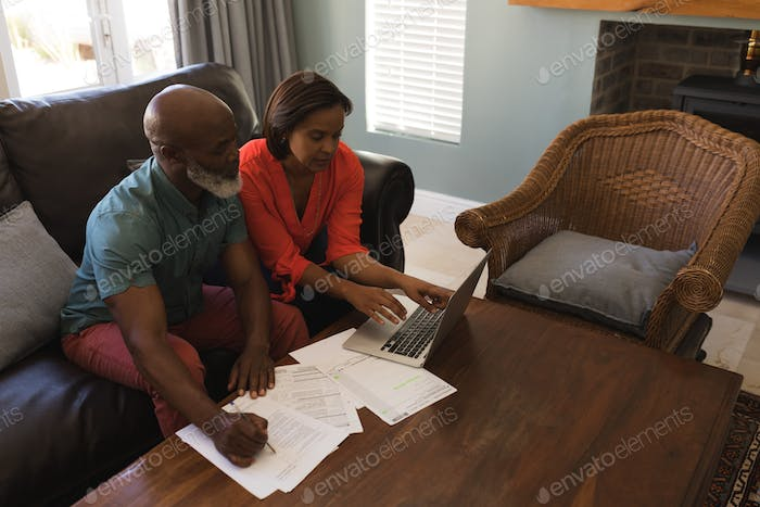 High angle view of a senior couple using laptop while sitting on a sofa in the living room at home