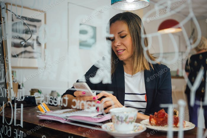 Smiling woman using cell in cafe