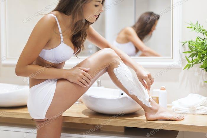 Focus woman shaving legs in bathroom