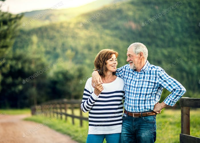 A senior couple in love looking at each other outdoors in nature. Copy space.