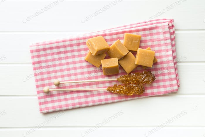 Brown sugar crystals on stick and caramel candies.