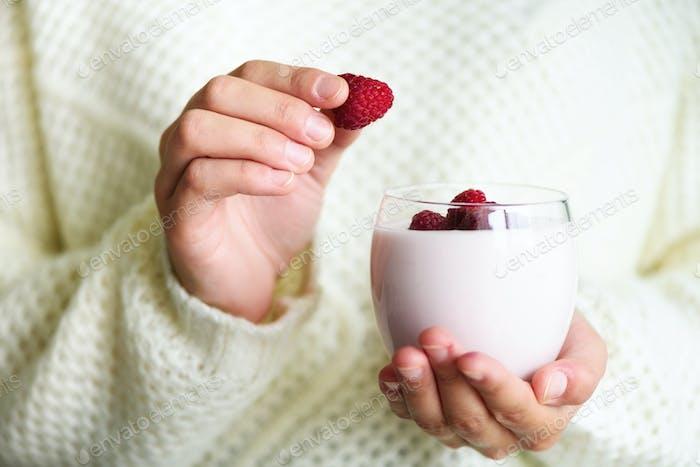 Girl holds glass of milk or yogurt, kefir with raspberries. Healthy and clean eating. Copy space