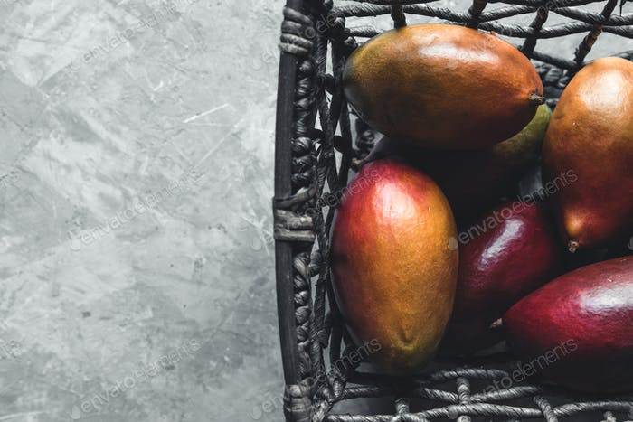 large mangoes in a wicker basket on a gray background. Healthy food, vegan