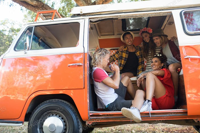 Happy friends sitting together in camper van