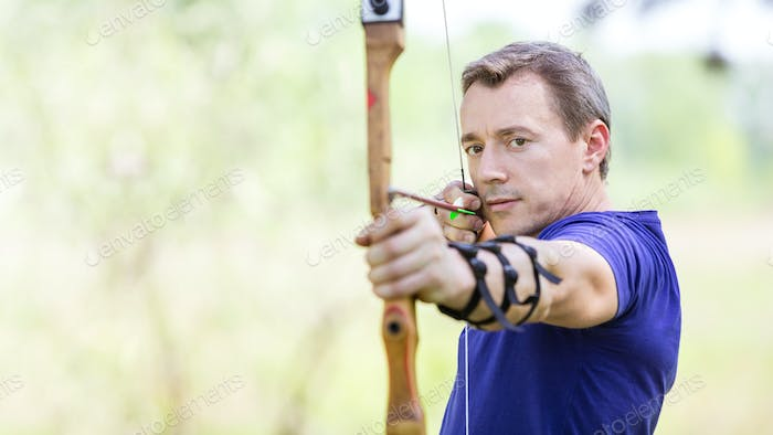 Bowman aiming arrow at target