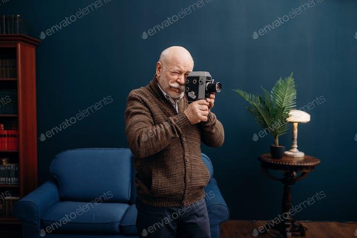 Hombre anciano posa con cámara de cine vieja