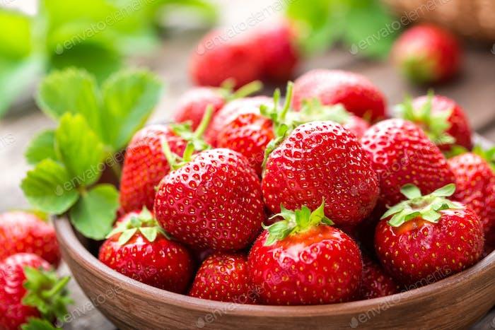 Erdbeere. Frische Erdbeere mit Blättern auf Holztisch