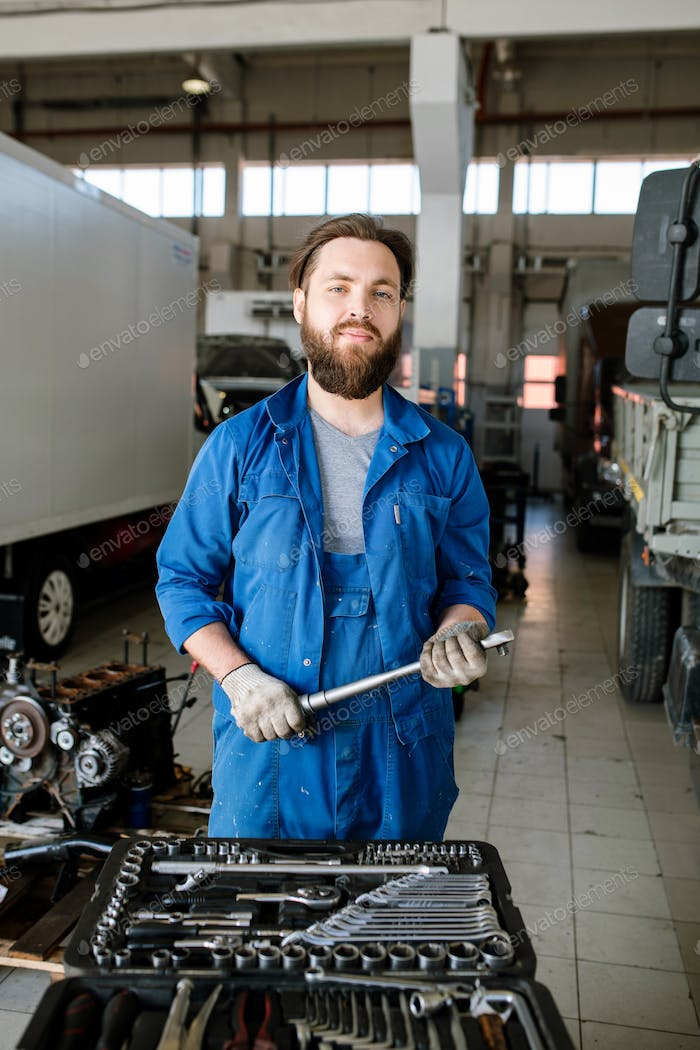 Young bearded master of technical repair standing inside workshop