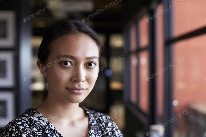 Millennial Asian businesswoman by window in office looking to camera, head and shoulders, close up
