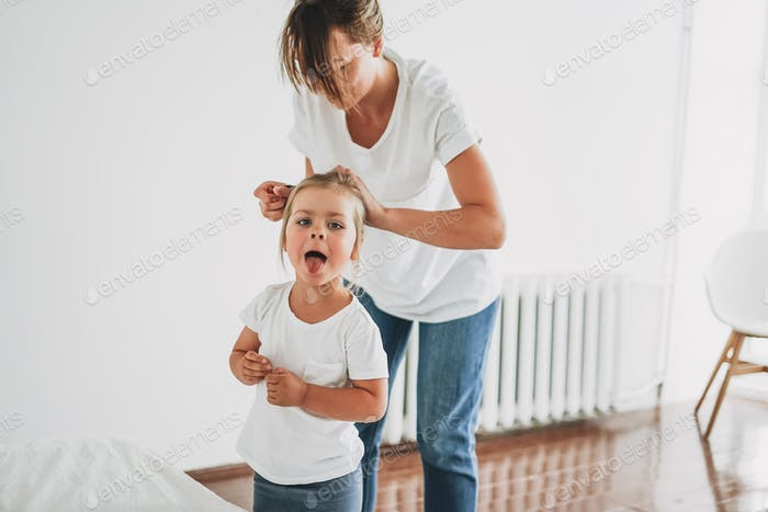 Funny moment of real life when young mother doing to daughter toddler girl pony tail