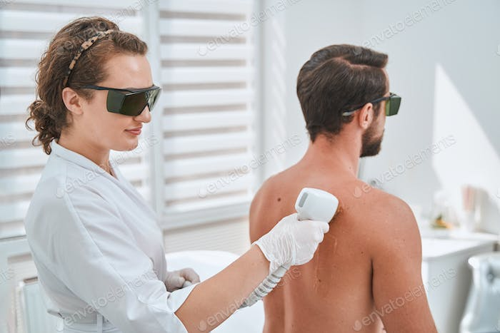 Female doctor in safety goggles performing an aesthetic procedure